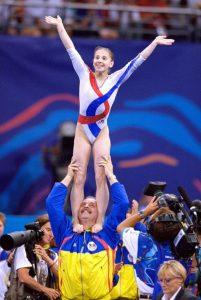 Andreea Raducan celebra el título olímpico individual junto a su entrenador: Ezra Shaw-Allsport.