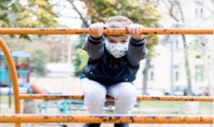 Niño jugando en el parque con mascarilla: RF.